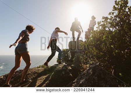 Young People On Mountain Hike On A Summer Day