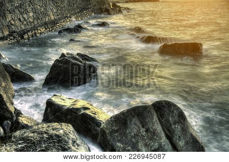 Waves Over Rocks At Sunset On The Bay Of Biscay Beach, Spain