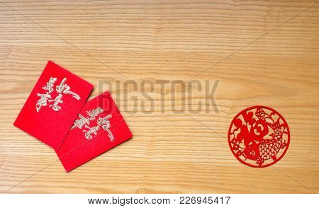 Traidtional Chinese Red Pockets And Paper Cut On Table  The Chinese Means Everything Is As Wishes