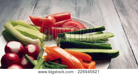 White Plate With Vegetables For A Vegetarian Salad. White Wooden Kitchen Table. Radishes, Tomatoes,