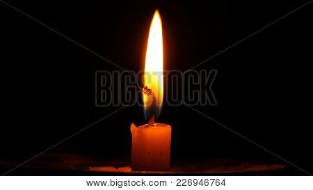 An Isolated Burning Candle Flame On A Black Background