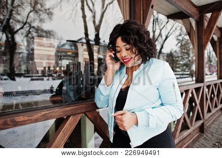 Stylish African American Plus Size Model With Mobile Phone At Hand Against Wooden Cafe At Winter Day