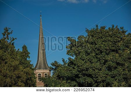 Tree Tops And Bellow Tower Roof At Sunset And Blue Bright Sky In Tielt. Charming And Quiet Village I