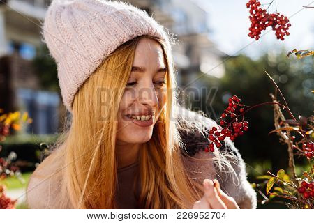 Happy Beautiful Blond Girl In Hat Walking In The Garden, Smiling, Looking At The Berries