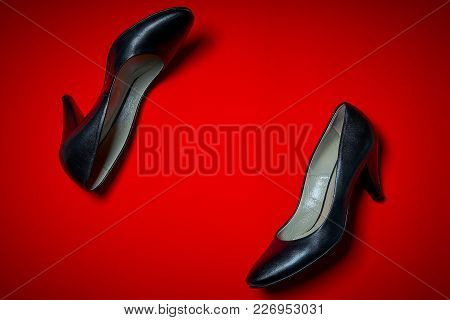 Top View Of A Pair Of Black High Heels On An Intense Red Background