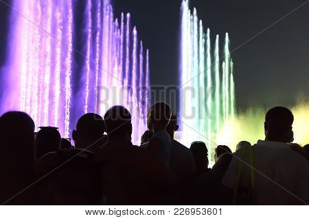 At The Evening Performance People Admire And Take Pictures Of The Color-music Fountain.