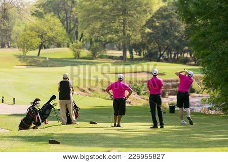 Group Of Golfers On A Fairway Watching A Tee Off