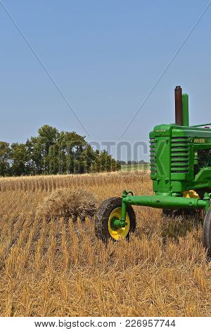 Rollag, Minnesota, Sept 2, 2017:  The Front Wide Wheeled A John Deere Is In A Wheat Field Participat