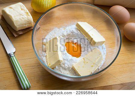 Ingredients For Christmas Cookies In A Bowl - Flour, Sugar, Egg Yolk, Butter, Grated Lemon Bark
