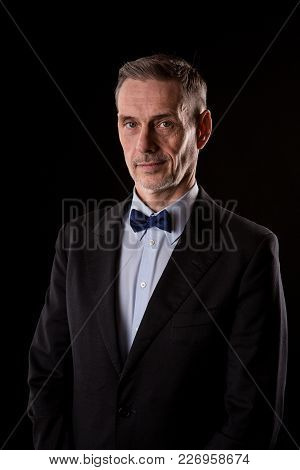 The Older Businessman In A Suit With A Bow Tie On Black Background. Studio Shoot