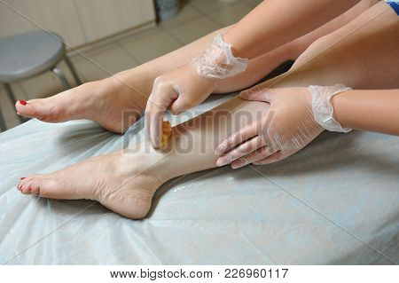 Removing Unnecessary Hair On The Legs. Procedure Sugaring In A Beauty Salon. Sugar Depilation