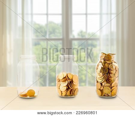 Concept Of Investment Or Savings For Retirement With Three Glass Jars Filled With Gold Coins In Fron