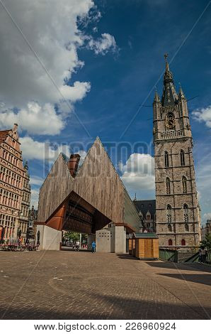 Modern Building And Old Clock Tower With Clouds And Blue Sky In Ghent. In Addition To Intense Cultur