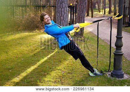 Man Fitness Model In A Blue Sport Jacket Doing Workouts With Fitness Trx Strips In A Park.