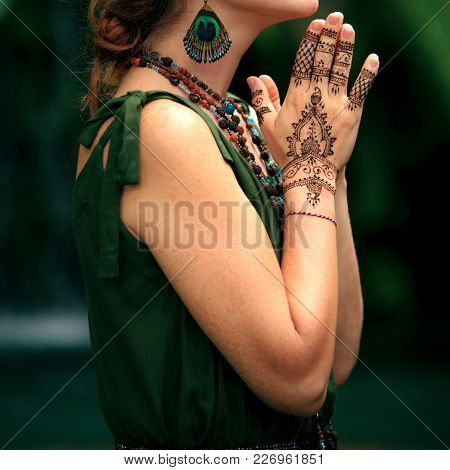 Female Hands With Henna Tattoo Praying. Beautiful Indian Mehendi Ornaments Painted On A Body Part