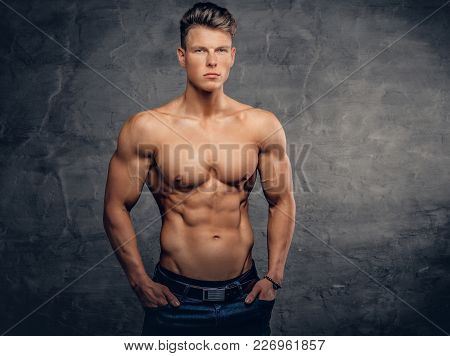 Portrait Of Shirtless Strong Suntanned Muscular Male Over Grey Background.