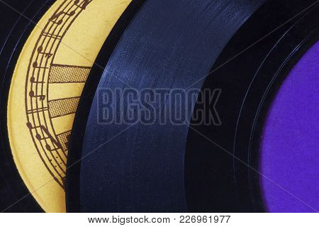 Stacked 45 Rpm Records Contrast Purple, Yellow, And Black With A Border Of Musical Staff And Notes
