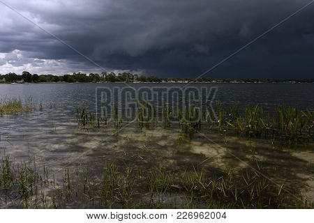 Dark Storm Clouds Gather Over South Lake Conway In Belle Isle, Florida Near Orlando.