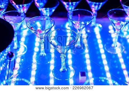 Empty Glasses Of Cocktails At The Holiday Party With A Bright Blue Backlight