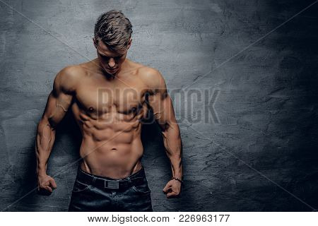 Portrait Of Shirtless Strong Muscular Guy On Grey Background.