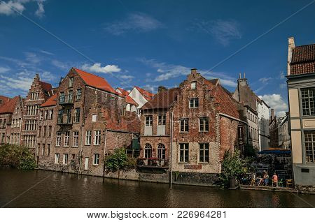 Ghent, Belgium - July 03, 2017. Old Buildings In Front Of The Canal And People In Ghent. In Addition