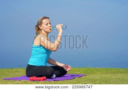 Young Woman Is Drinking Water From A Bottle While Sitting On Yoga Mats On The Grass On The Backgroun