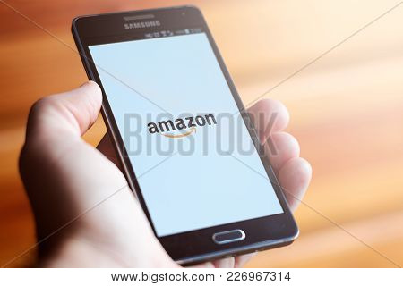 Buenos Aires, Argentina - February 16, 2018: Hand Holding A Mobile Phone Showing The Amazon Logo Of