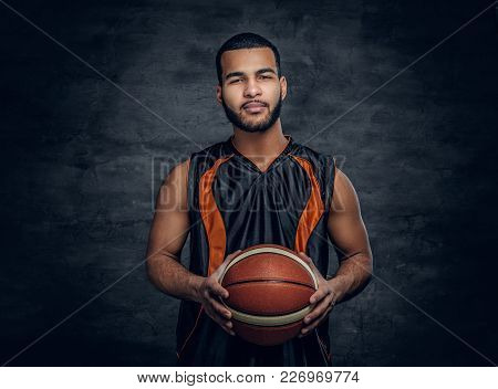 Studio Portrait Of Black Basketball Player Holds A Ball Over Grey Background.