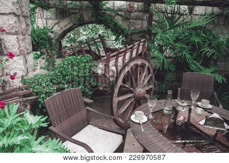 Restaurant Balcony Interior With Vintage Wooden Wagon, Garden Furniture And Beautiful Green Plants