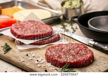 On A Wooden Cutting Board On Kraft Paper There Are Raw Beef Burgers For Burgers, Spices, Rosemary, A