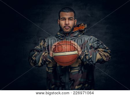 A Black Male In A Camouflage Hoodie Holds Basket Ball.