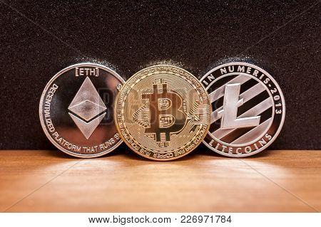 Three Coins Bitcoin Ligtecoin Ethereum Virtual Moneyon Wooden Background