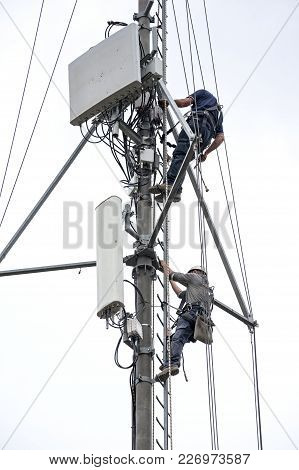 Two Workers With Harness Climb Up The Ladder Of The Antenna Tower