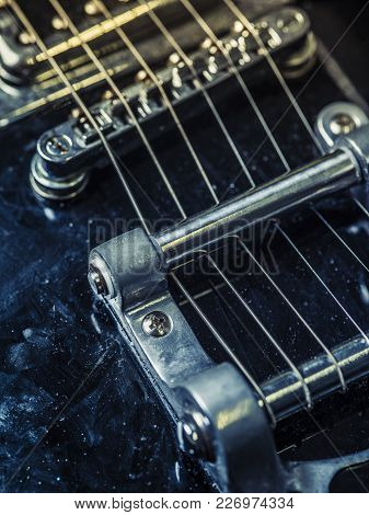 Macro Photo Of The Strings And Bridge Of An Old Electric Guitar.