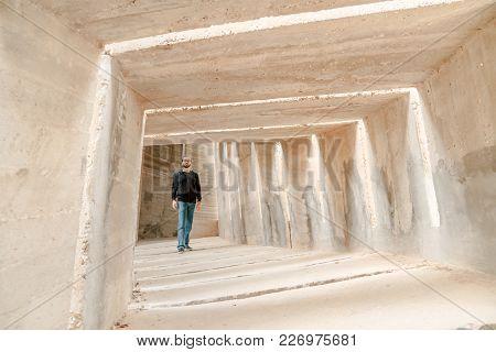 Front View Of Man Walking Alone In Tunnel Corridor. Urban Underground Lonely Walkway  Passage. Singl