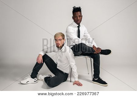 Joyful Relaxed African And Caucasian Boys In White And Black Office Clothes Laughing And Posing At W