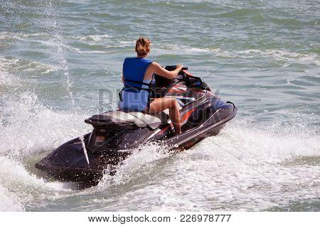 Woman Riding Waves On A Speeding Jetski On The Florida Intra-coastal Waterway Off Miami Beach.