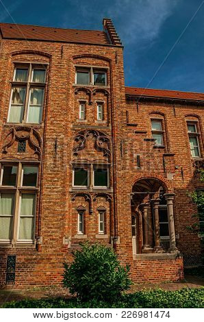 Brick Facade Of House In Typical Flanders Style And Blue Sky In Bruges. With Many Canals And Old Bui