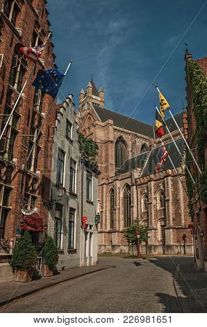Bruges, Belgium - July 05, 2017. Street With Flags, Brick Houses And Church At Bruges. With Many Can