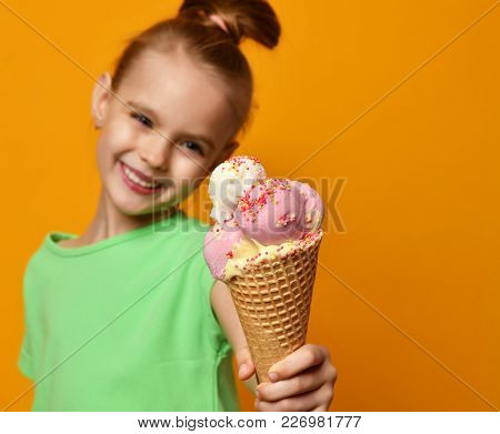 Pretty Baby Girl Kid Eating Licking Banana And Strawberry Ice Cream In Waffles Cone On Yellow Backgr