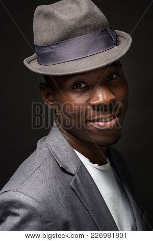 Portrait Of Attractive Young Black Male Studio With Hat Cheesy Smile On Dark Background. Studio Shot