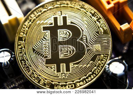 Golden Bitcoin Virtual Currency On A Circuit Board Background. Background Matherboard.