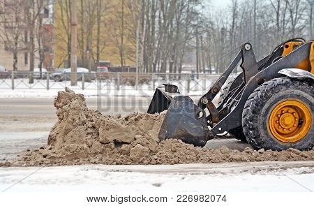 Part Of A Wheel And Ladle Of The Tractor Which Removes A Big Heap Of Snow With Sand And Reagents Fro