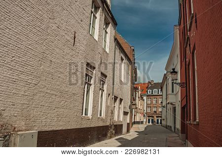 Quite Empty Street With Brick Buildings And Blue Sky At Bruges. With Many Canals And Old Buildings,