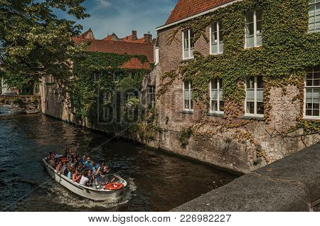 Bruges, Belgium - July 05, 2017. Tourist Boat On Canal And Brick Building At Bruges. With Many Canal