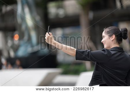 Portrait Of Excited Cheerful Smiling Young Pretty Woman In Suit Making Selfie Photo.