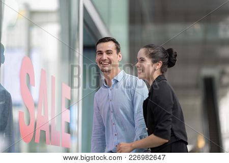 Woman And Man Excited Looking Into Shop With Shop Window Display With Text Sale On Red Poster.going
