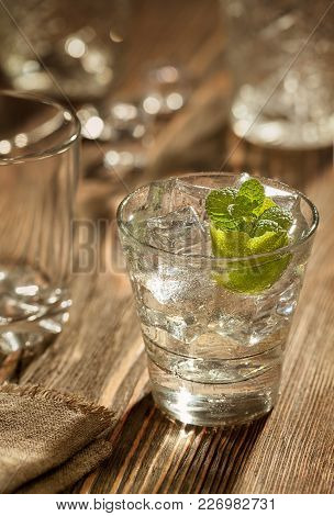 Glass Of Gin Tonic With Lime And Ice Over A Wooden Table. Close-up. Still Life. Copy Space