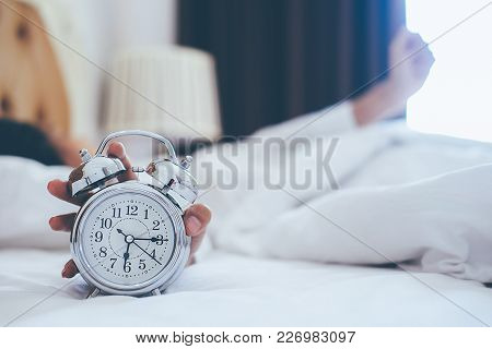 Irritated Young Woman Putting Her Alarm Clock Off In The Morning With Soft Morning Light. Relaxing C