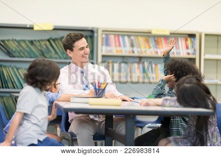 Happy Children And Teacher In Learning Class At Library. Boy Raised Hand Up His Hand To Answer A Que
